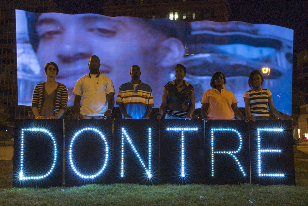 The family of Dontre Hamilton, including his mother Maria Hamilton and brother Dameion hold this message at Red Arrow Park, where Dontre was killed in April of 2014.